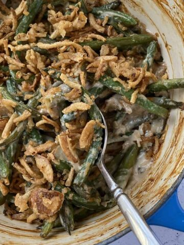 Baked green bean casserole with a serving spoon.
