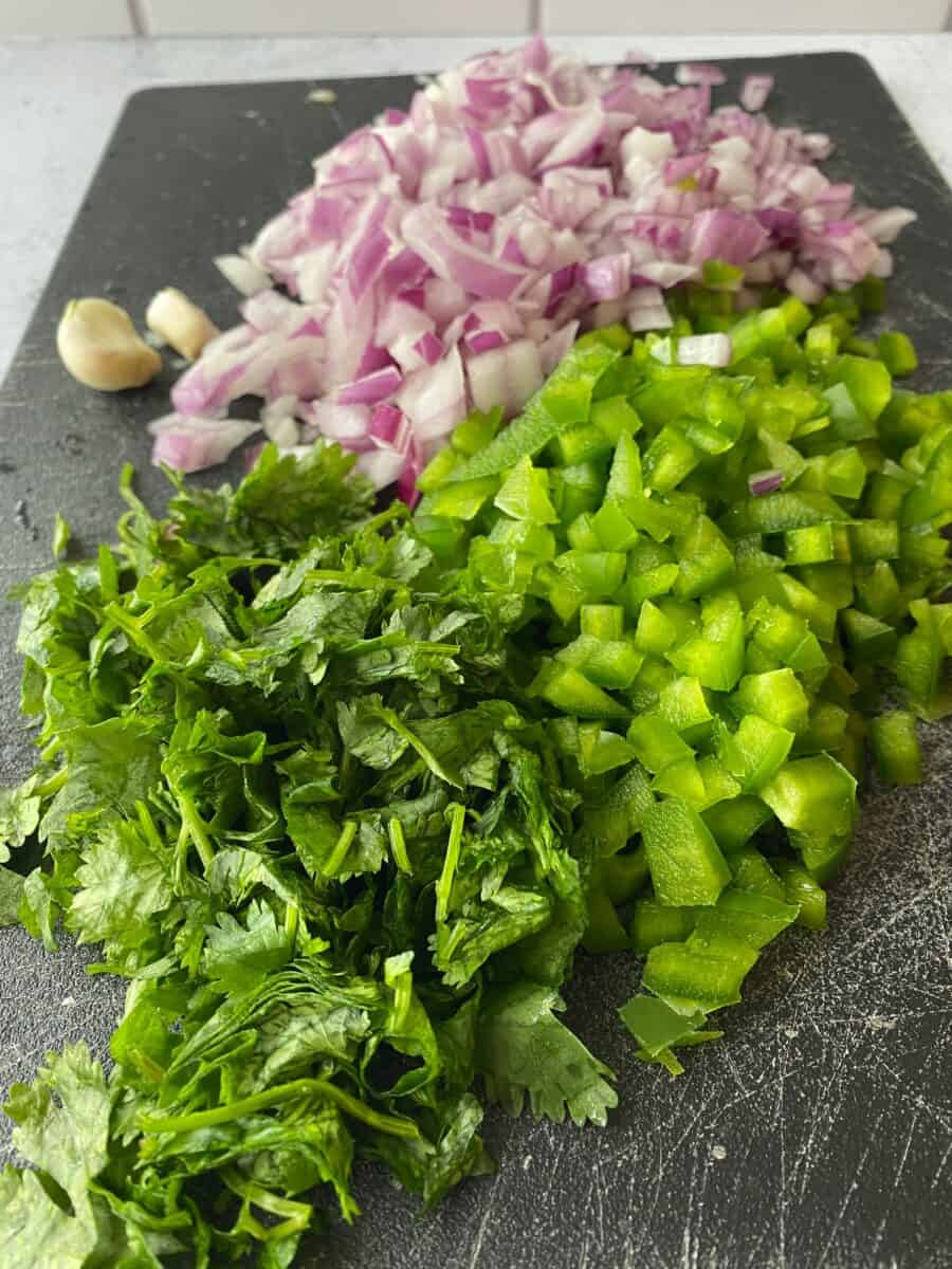Diced onion, green pepper and cilantro on a cutting board.
