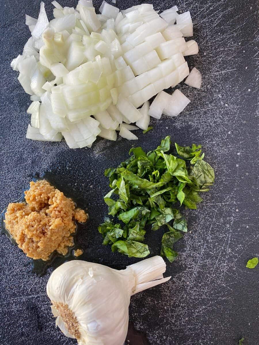 Chopped onion, garlic and basil on a cutting board.