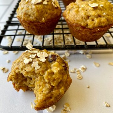 Banana carrot muffins with oats on a cooling rack.