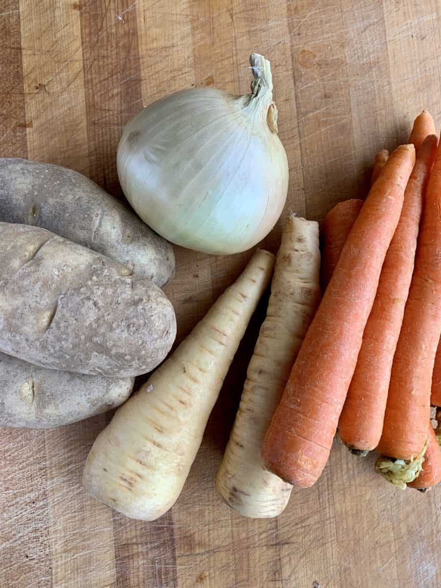Potatoes, onion, parsnips and carrots on a cutting board.