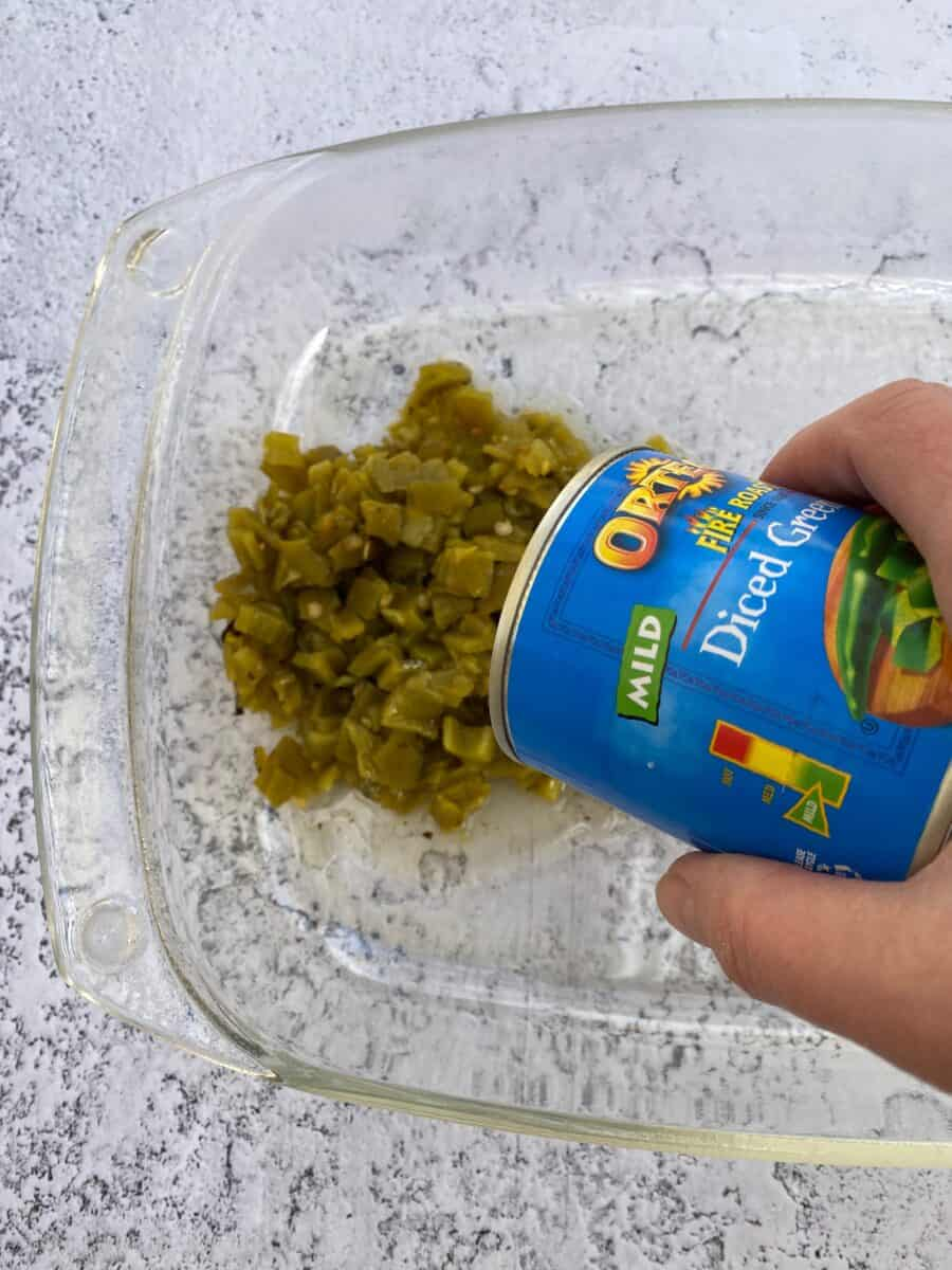 Canned green chilis being poured into a baking dish.