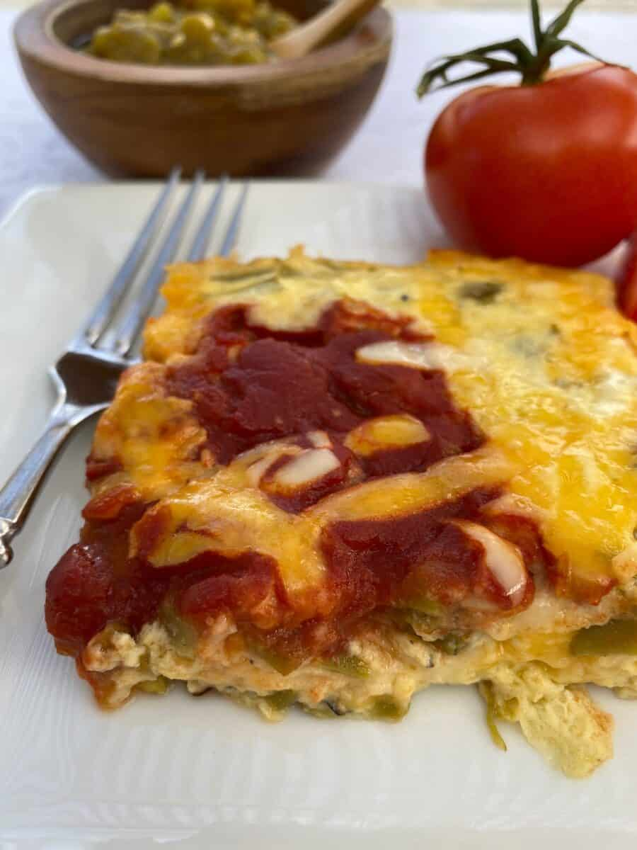 A serving of the chili relleno casserole with tomatoes and a small bowl of salsa.