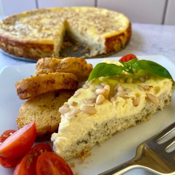 Slice of savory cheesecake with cherry tomato slices, small bread slices and a fork on the side. Whole cheesecake in the background.