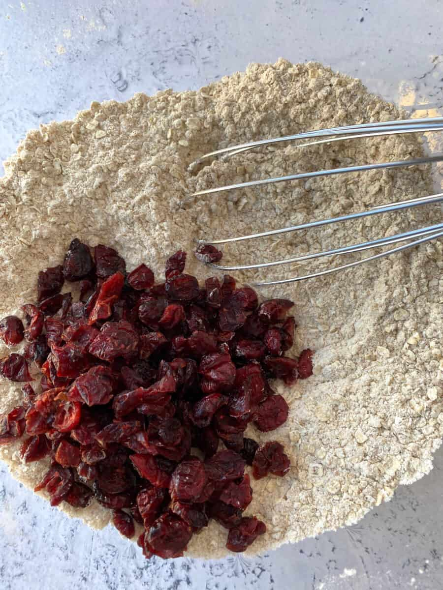 Dried cranberries and dry ingredients in a bowl with a whisk.
