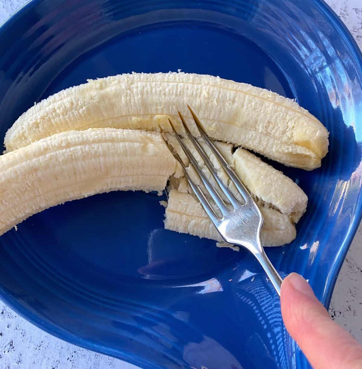 Two bananas in a dish, with a fork mashing them.