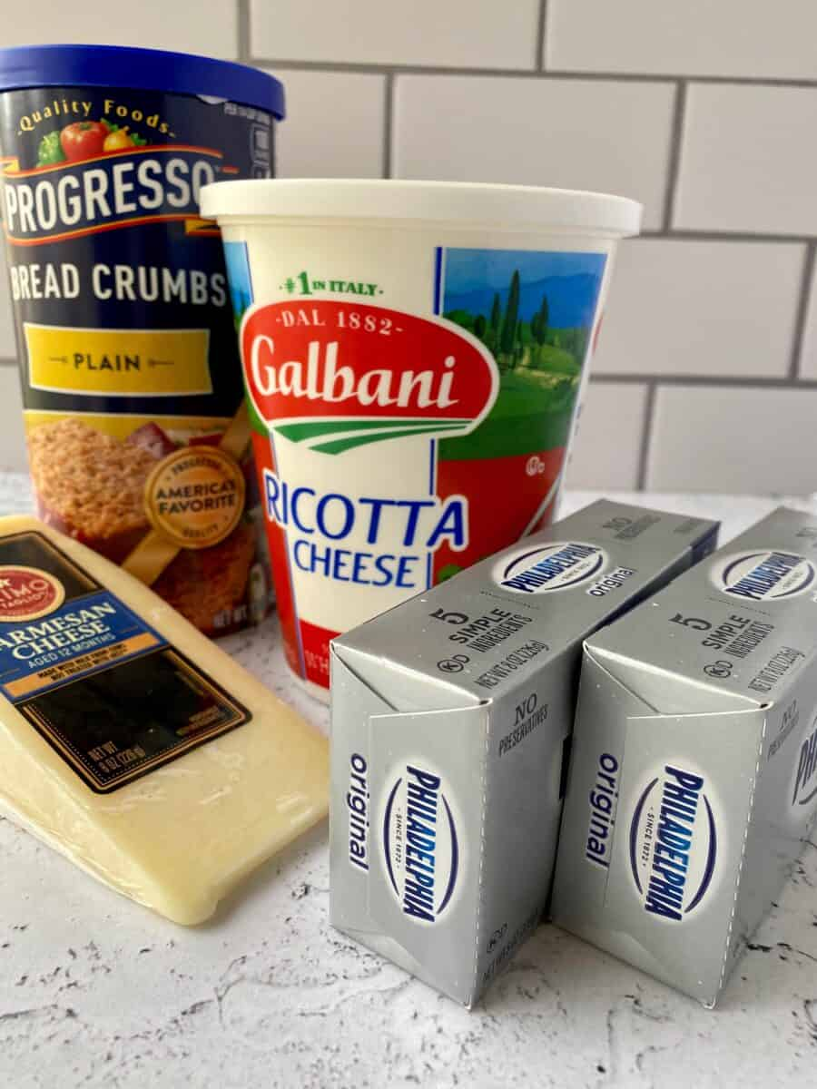 Cheesecake ingredients on a counter, cream cheese, parmesan cheese, ricotta cheese and a box of dry breadcrumbs.
