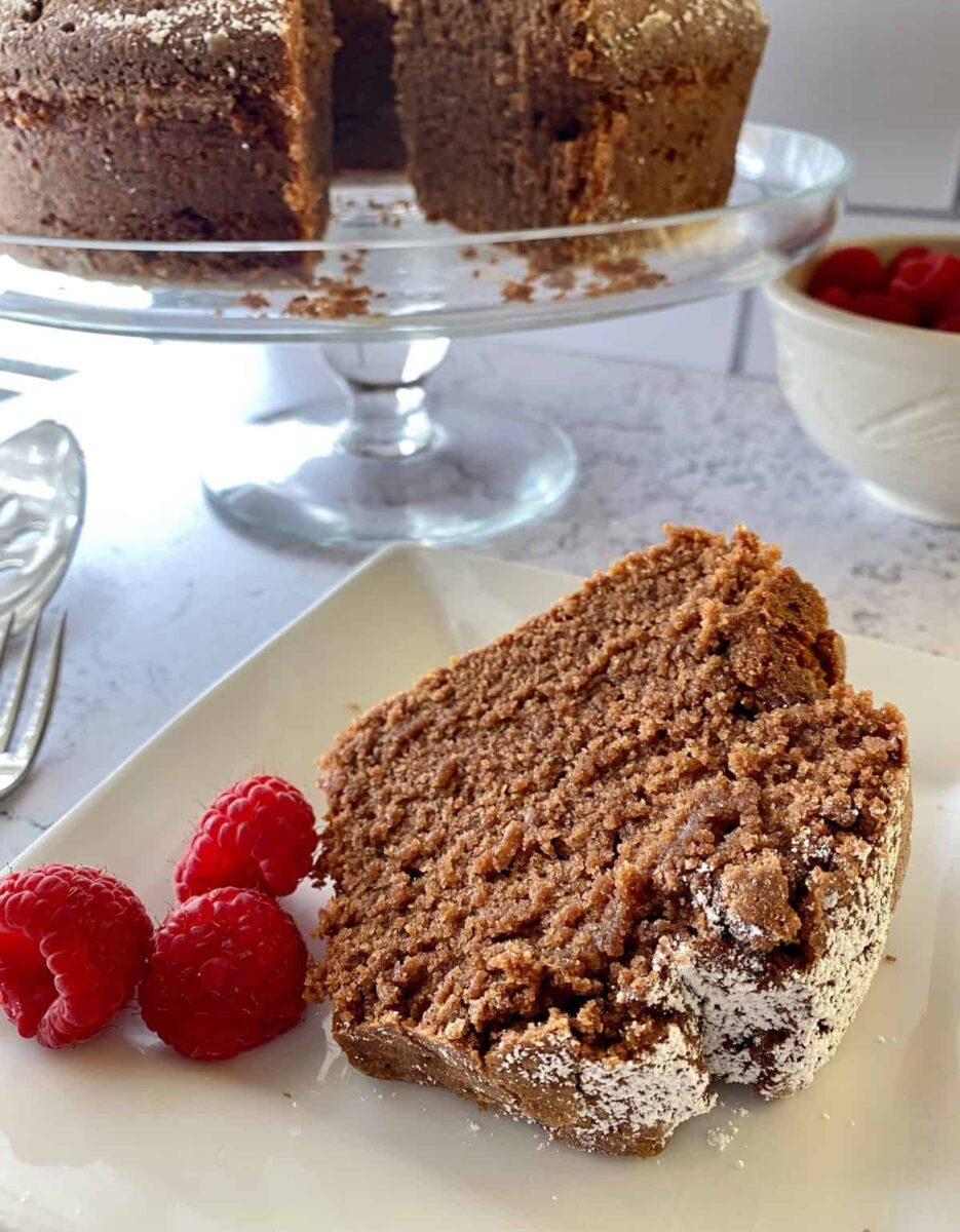 A slice of cake with raspberries with the entire cake on a serving plate in the background.