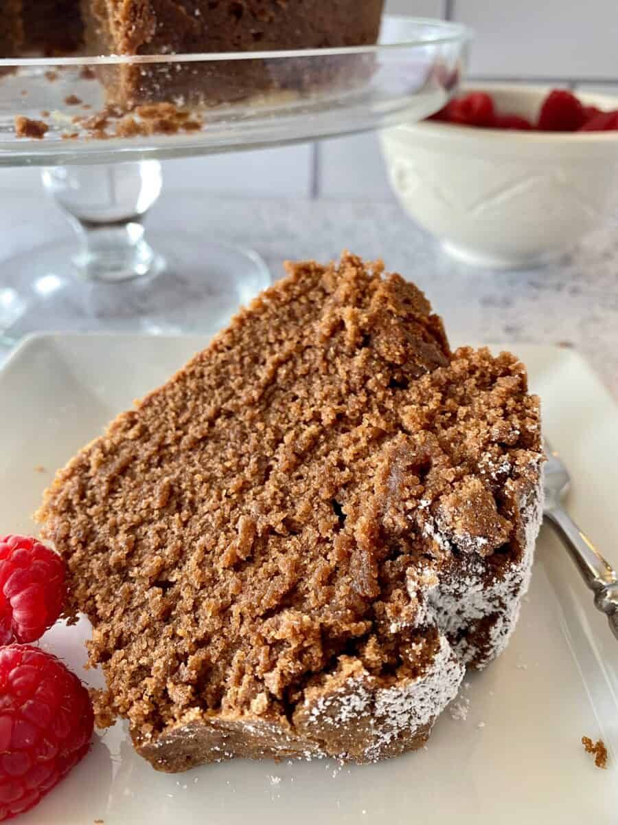 A slice of chocolate pound cake with raspberries on the side.