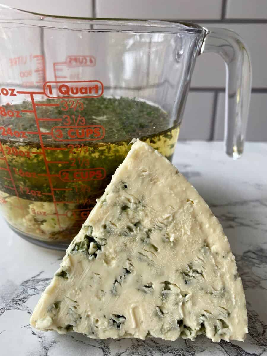 A wedge of blue cheese tipped on edge next to a glass measuring cup of salad dressing ingredients.