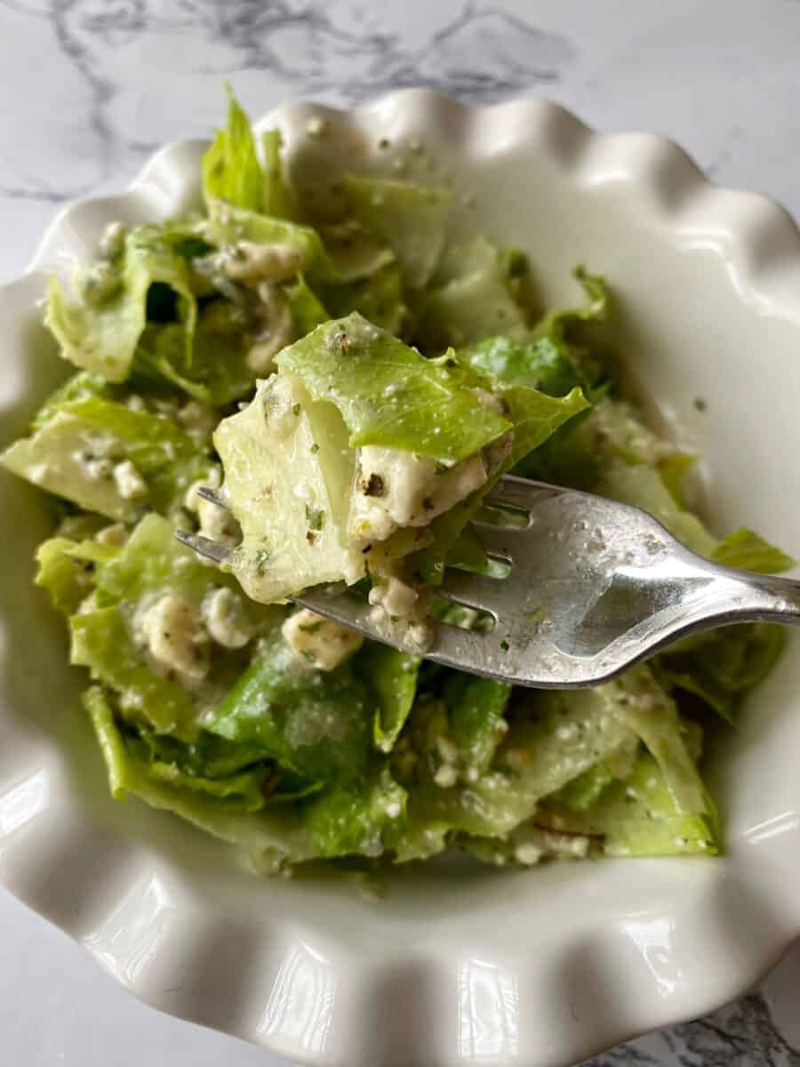 A fork full of green salad held above a bowl of salad.