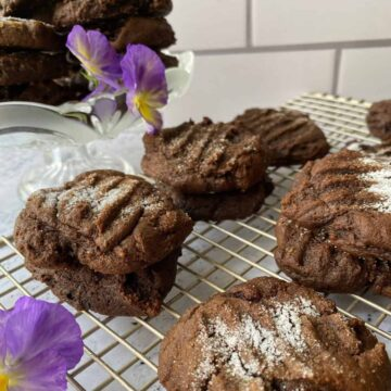Snaps on a cooling rack with a pansy on the side.