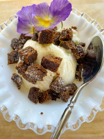 A scoop of ice cream with diced molasses snap on top and a pansy flower and spoon.
