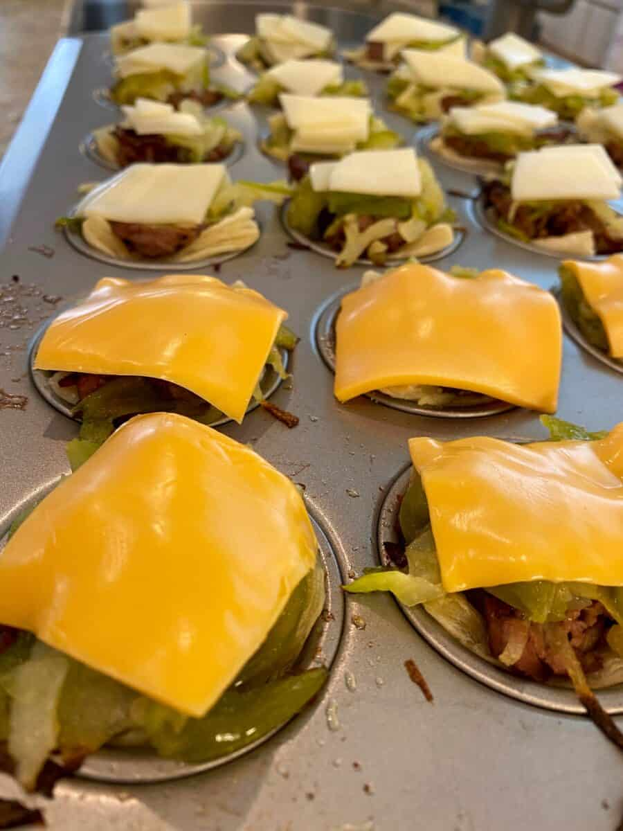 Mini Philly Cheesesteaks in a mini-muffin pan with melted cheese on top of each one.