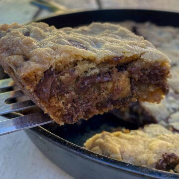 Chocolate chip bar cookie on a spatula, lifted out of a cast iron skillet on an outdoor table.