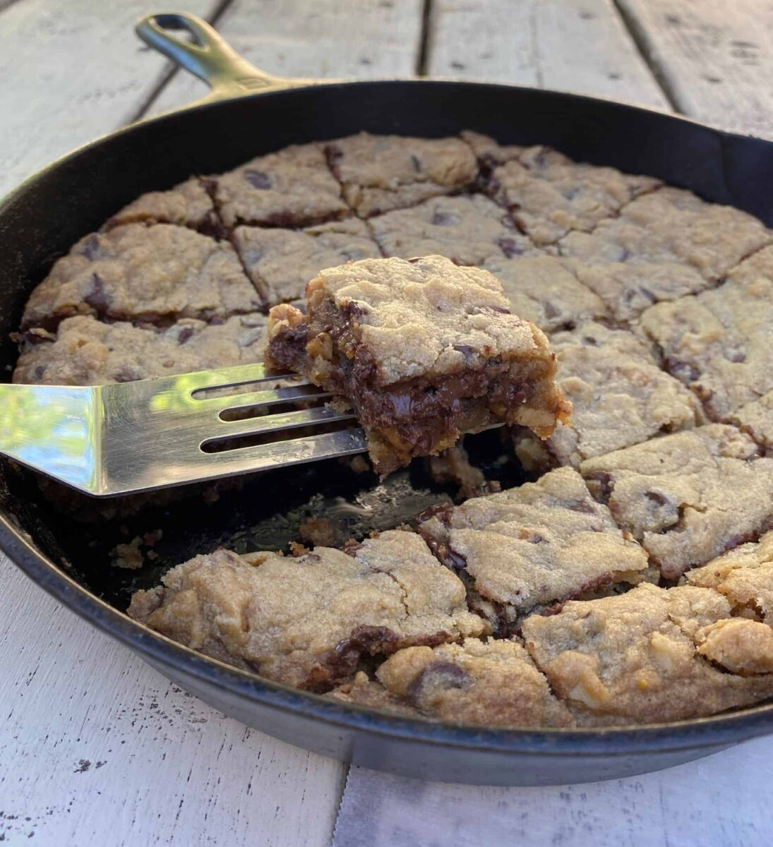 Chocolate chip bar cookie on a spatula, lifted out of a cast iron skillet.