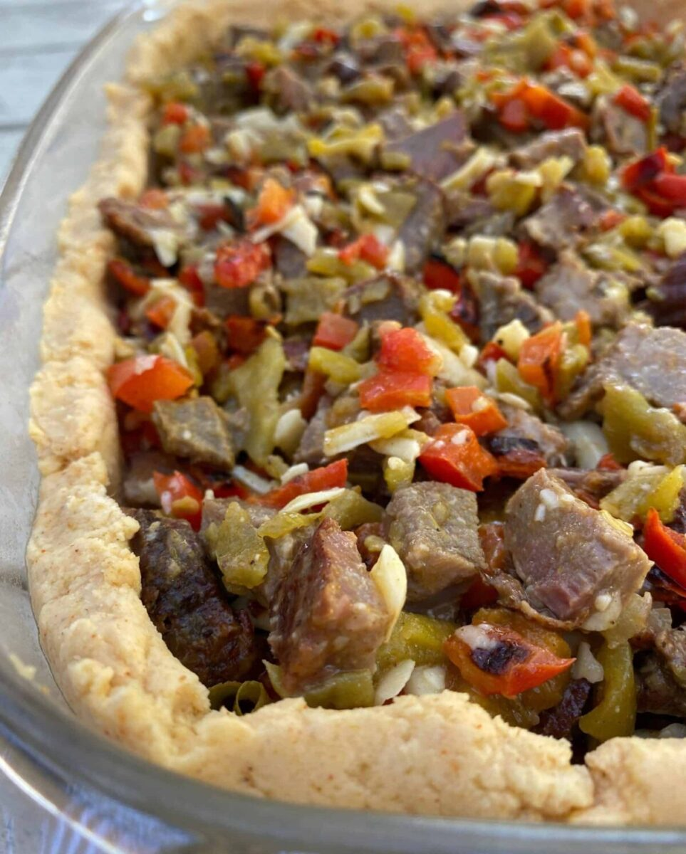 Diced beef with red peppers and green salsa in a tamale crust, all placed in a large glass dish.