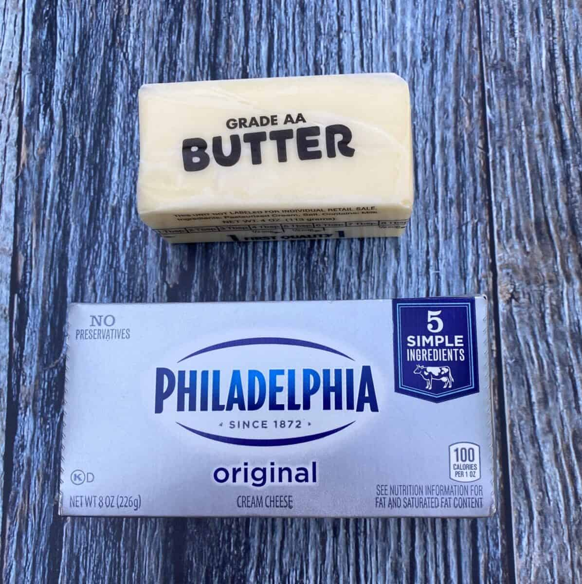 A stick of butter and a package of cream cheese on a wood block.