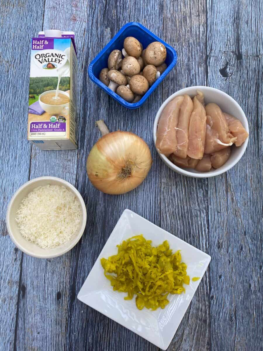 Spicy Chicken Alfredo ingredients on a wooden block, displaying a carton of half and half, mushrooms, uncooked chicken, a sweet onion, grated parmesan cheese and a plate of pepperoncinis.