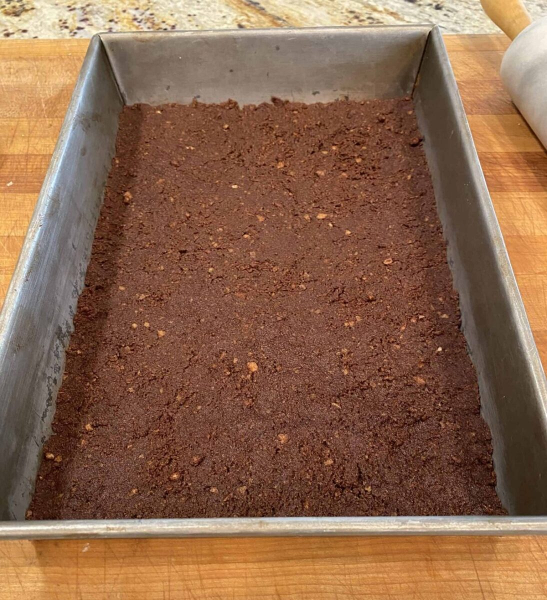 Chocolate vanilla wafer crust in a baking pan.