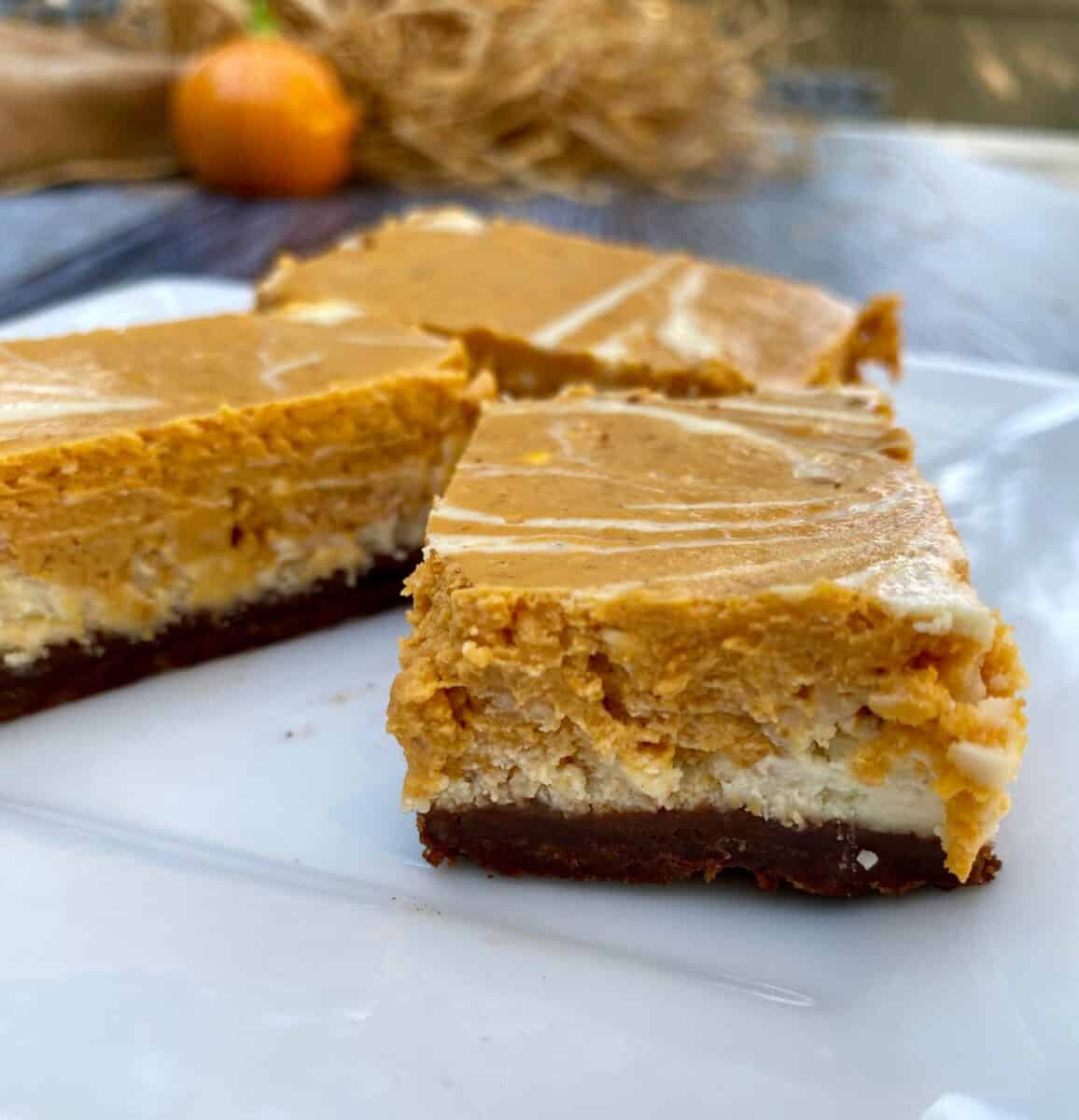 Three portions of pumpkin cheesecake bars on a plate with a small pumpkin and straw in the background.