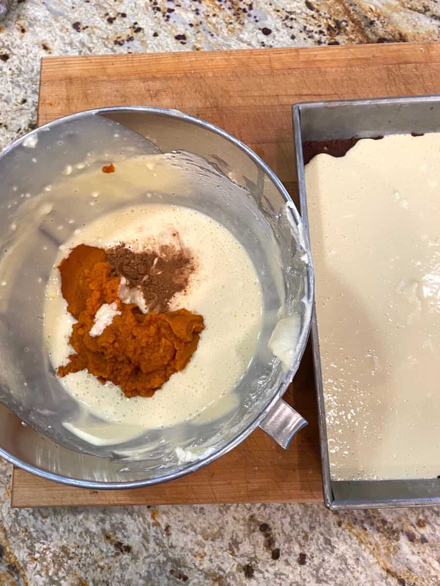Pumpkin mixture and spices in a mixing bowl next to a pan of cream cheese batter.