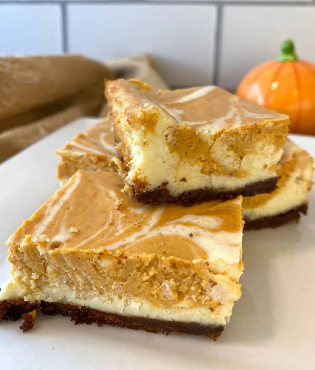 Three baked cheesecake bars stacked on a plate.