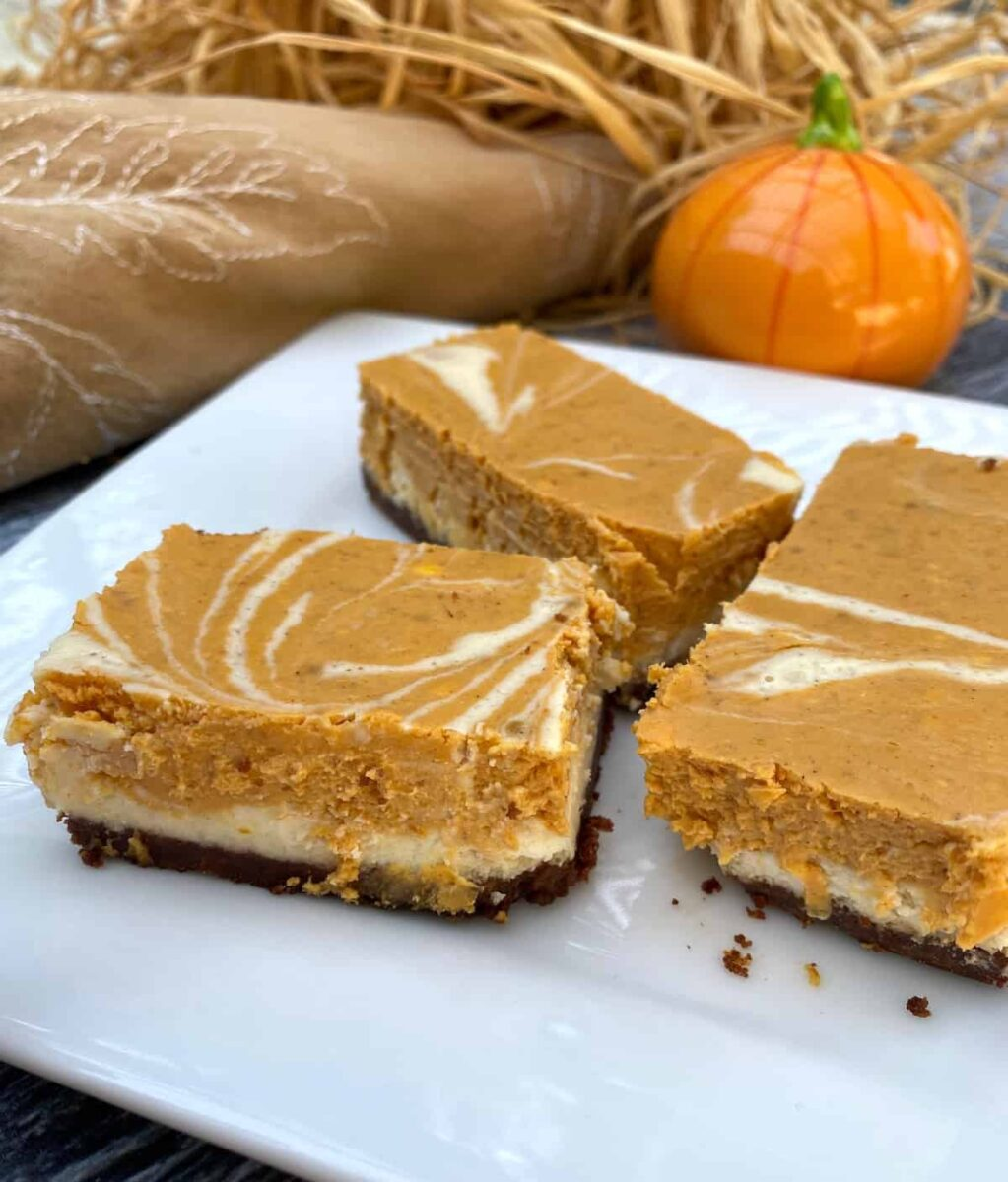 Three pumpkin cheesecake bars on a plate with straw and a miniature pumpkin ornament in the background.