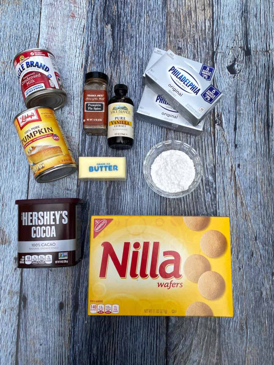 Ingredients for marbled pumpkin cheesecake bars, spread out on a wooden board.